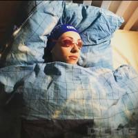 zu sehen ist eine junge Frau mit Schwimmbrille und Badekappe im Bett. Sie träumt vom Training.